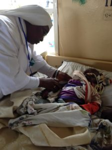 Sister Doreen provides nutrition assessment for a malnourished child in the Children's Ward at Mbingo Hospital, July 2015.